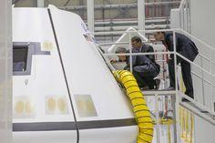 Bob Cabana, John Mulholland and Jorge Hernandez look at a Boeing CST-100 Starliner spacecraft mock-up