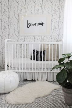 Gender neutral nursery perfect for baby girl or boy. Grey wallpaper creates interest in this baby room.