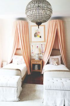 Children's bedroom with matching canopy beds and a large chandelier