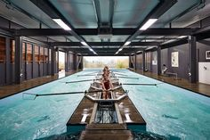 A pool with a stationary boat on top is the centrepiece of this rowing centre designed for a private boarding school