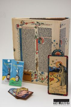 "The Frist Center offers gifts inspired by the exhibition Sanctity Pictured. Handcrafted retablos are available in pocket & ornament sizes w/illustrations of religious figures and their quotes carved on the back. Pocket size retablos are $6 and ornament size retablos are $16. ""Tiny Saints"" keychain allow you to conveniently carry a saint along w/you for $5 each. Paper Blanks represents the detailed and colorful Gutenberg bible through the cover of this notebook for $22.95"