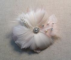 This romantic one of a kind feather corsage is sure to be a beautiful compliment to your wedding day! Each flower is hand crafted with the best quality silky feathers and your choice silver or gold rhinestone brooches and accents. The corsage shown is made in soft shades of ivory with blush pink accents. Feather flower available in white, ivory, blush pink, black, champagne, coral, burgundy, purple, lavender, grey, dusty rose, turquoise, navy blue and royal blue with your choice ribbon…