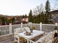 Balcony/deck: white wooden balustrade, white wooden table and benches, grey timber decking