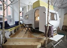 A hotel with indoor caravans and huts for rooms.