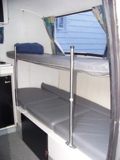 narrow bunk bed over couch over storage.