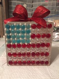 I love Americana and being at the USA Swim Olympic Trials has got me pumped! This project is guaranteed to bring out the USA spirit! This is a very easy and fun project. You will need glass marbles, a glass block, pearls and glass glue, ribbon.