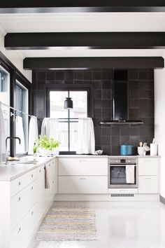 Keittiön päätyseinä on laatoitettu Pukkilan mustalla Via Emilia Nero -laatalla. Musta liesituuletin on Franken mallistosta. Helena Karihtala suunnitteli muutama vuosi sitten Topikeittiöille yksinkertaiset Lato-keittiökaapistot, joiden ovet saivat nyt uuden harmaan sävyn.