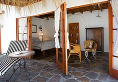 Syros Room  A bright and airy studio with high wood beam ceilings, a Queen bed and stone floors. It also features a beautiful slate bathtub and shower. French doors lead to an open patio. Room includes homemade breakfast daily.