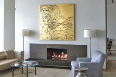 Modern linear gas fireplace with cantilevered stone and blackened steel surround.