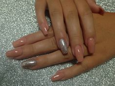 Nude coffin acrylic nails with silver glitter accent.