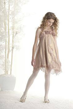 Biscotti Shimmering Rose Strappy Dress in gold. This ethereal gold dress in fluttery chiffon looks like it's been dipped in magic! The cascading ruffles, three dimensional flowers and asymmetrical hemline are perfect for the young princess in your life.