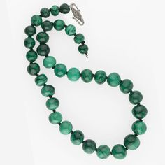 A necklace of fabulous irregular hand cut malachite beads graduated from 17mm to 11mm.  The beads are wonderfully irregular in shape with gorgeous shades of green and a high polish. Some of the beads are banded, some are marbled. Shades of green from a rich teal to dark green. Each one is spectacular. Each bead is hand knotted. One smaller bead has a chip near the hole and that is not easily visible. Sterling silver embossed S clasp. 20.5 inches. 172.7 grams. The necklace is newly strung…