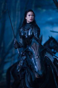 dark female warrior knight on black horse in black forest lit by hellish blue eyes