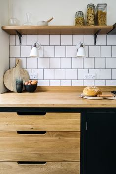 Oak and birch plywood flat panel kitchen cabinetry with three drawers, oak worktop and shelving with a white square tile splashback. The kitchen cabinets are painted in Little Greene Obsidian Green. Wall lights from Original BTC.