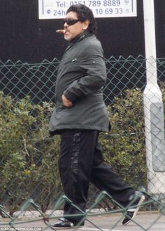 Taking a stroll: Cigar in mouth and football boots on, Argentinian legend Diego Maradona goes for a stroll through Manchester