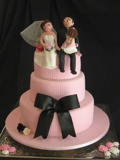 Ashley and Mitchell - Pink Textured Wedding - Three tiered round wedding cake, covered in pink fondant with vertical fine lines embossed all around each tier. Fondant covered board, non-edible silver beading. Fondant black ribbon bow. Pink, white and black sugar roses. Hand-modelled figurines of couple with their 3 year old daughter. Thanks for looking.