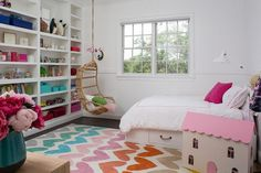 White and pink girl's room boasts a white storage bed dressed in pink border hotel bedding and shams and positioned on a colorful heart patterned rug facing a floor to ceiling built in shelves fixed behind a Two's Company Hanging Rattan Chair hung beside a window framed with white beadboard trim accented with a chair rail.