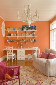 Orange walls patterned artwork and light carpets add to the