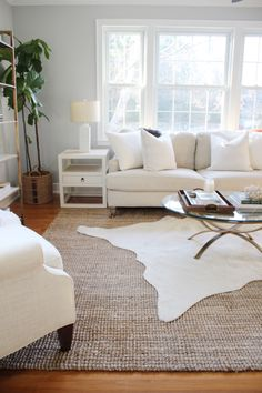 We love how the positioning of the faux cowhide over the jute rug helps anchor the coffee table in this airy living room.
