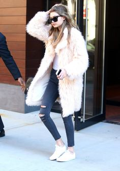 Gigi Hadid weras a pink Elizabeth and James coat, ripped jeans, and white sneakers
