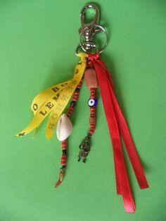 Chaveiro com argola e mosquetão, feito com miçangas, contas, fitas, búzio, olho grego e pimenta de murano, uma peça de cerâmica e pingente de Exu