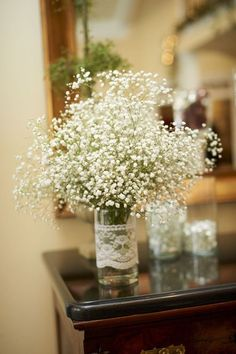 babys breath in mason jars- Something like this with gloss rocks at bottom, lace and candle?