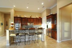 Gorgeous kitchen with cherry cabinets, stainless appliances and polished travertine floors