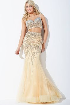 Styled in tulle, this Jovani JVN63891 two-piece prom dress has a trumpet silhouette and features a beaded sweetheart crop top with illusion jewel neckline. The sleeveless top has a full illusion back and is paired with a full-length skirt with sweep train. Beads adorn the skirt through the hips, above filmy godets.