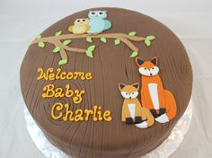 Woodland-themed baby shower cake with handmade fondant foxes and owls.