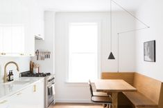 The countertop and backsplash are bianco gioia marble, and the apartment is painted throughout in Wevet by Farrow & Ball. The kitchen window has its original casing.