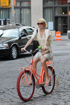 Erin Fetherson on a pink bike. Love everything : the colors, the dress, the hair, the bag, etc...