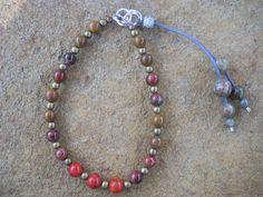 Red coral, leopardskin jasper, red chrysocolla and brass bead bracelet with unakite clasp detail. (BR6) $20. www.feeko.co.za