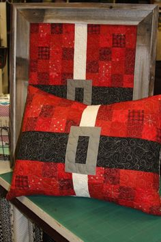 Quilted red plaid, polka dots pillow made to look like it has a black belt with buckle. Unique Christmas decor that could even be translated into an actual quilt.