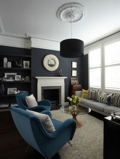 Living Room Sofa Design. low key love the paint on the wall. as for those 2 blue whatever they are called, not so sure about them. the design and colour.