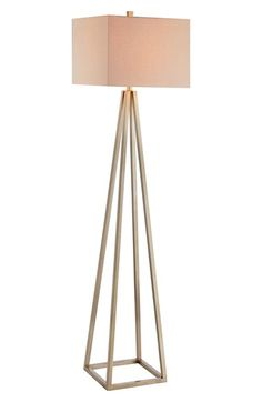 A statement-making floor lamp set on a caged metal pyramid base for a contemporary geometric aesthetic. Nordstrom