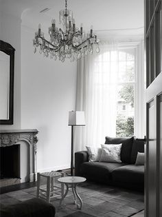 Love this combination of classic vs. modern design the fireplace and chandelier vs. modern couch sofa Piet Boon Klaar light high windows