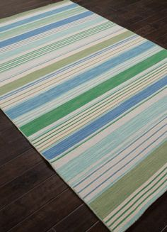 A decidedly beach style with coastal stripes of light green, aqua and blues with light grey, this area rug evokes a windswept day spent among the sea grass and sands of the shore dunes.