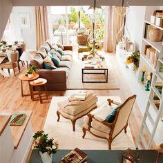 Salón con zona de lectura, lámpara de techo cristal, mesas de centro y de apoyo, butaca con banqueta y alfombras