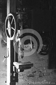 This is a black and white image of a vintage hand crank drill press with a rustic old grainy high contrast feel.