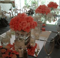Feasting table with several cube arrangements of Marylse Roses placed on mirror tiles with several votives betweenvendors: Flowers by Fudgie