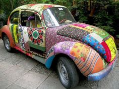 LoveBug ArtCar... Inspiring! I'm totally working on my own car in my mind, and this one is cool-- I like the patchwork quilt craziness, and it could save a lot of time to just apply big swatches of fabric like this. I wonder how they applied the fabric to the body of the car?