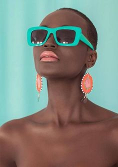 I love the combination of turquoise and coral! Square turquoise sunglasses, coral lipstick and earrings; dark skin, short hair.