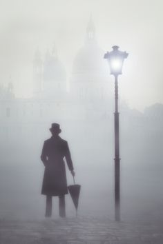 a victorian man with a top hat and an umbrella next to a street lamp in fog in front of a church