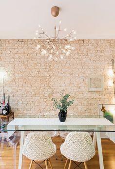 Sala de jantar com parede de tijolo,  mesa com tampo de vidro e cadeiras assinadas.