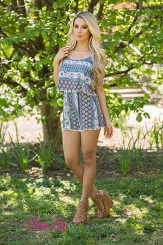 This romper is perfect for all of your summer adventures! From weekends at music festivals to cookouts in your backyard, this dreamy romper will be your favorite summer outfit! The bold fabric features a variety of geometric and floral patterns in turquoise, navy, orange, burgundy, hot pink, and off-white. The top is double-layered for a sweet ruffled detail, while the pom pom details on the hemline of the shorts and ruffled top add a little extra whimsy.