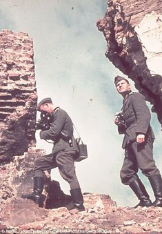 Two official Nazi photographers clamber around trying to take pictures.