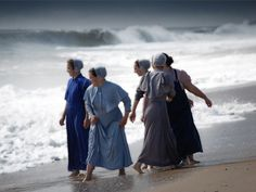 """'Littoral Women' lit·to·ral [lit-er-uhl] adj.: Pertaining to the seashore. Mennonite girls brave Hurricane Bill's monster waves in Rehoboth Beach, DE."""