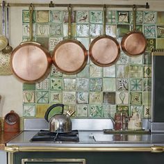 Copper pans compliment hand-painted ceramic tiles from Carreux de Chesley. #kitchens #kitchendesign. http://www.hglivingbeautifully.com/2015/02/27/splashback-ideas-for-stylish-kitchens/