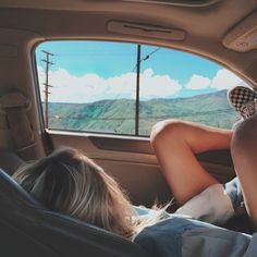 girl car window clouds green grass mountains clouds blonde