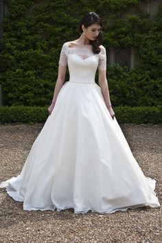 Sian- Augusta Jones Demure elegance. This lovely wedding gown features a lace boatneck bodice with sheer sleeves that just clip the shoulders. The A-line organza skirt flows out from a tiny satin belt at the waist. Covered buttons add the finishing touch.